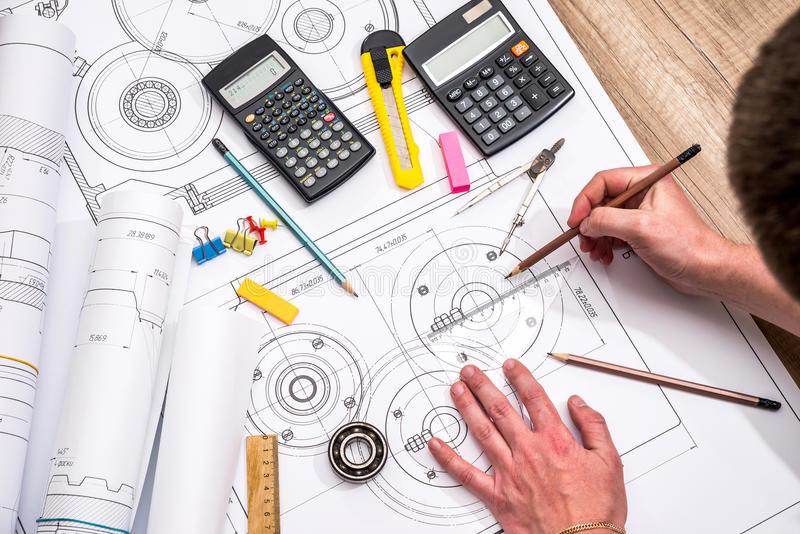 mekanisk-tekniker-med-arbete-på-tekniska-teckningar-97241972