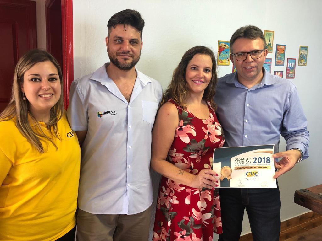 Vivian Lima e Douglas Silva, à direita, entregam o certificado à equipe da agência Itapeva Viagens