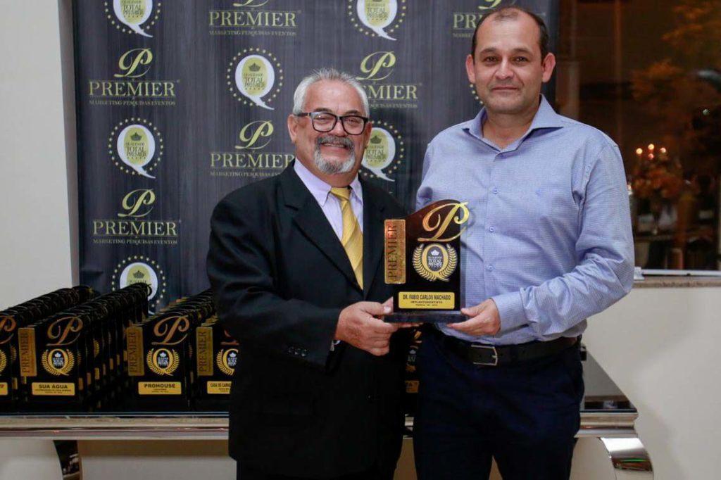 Dr Fábio, à direita, recebe o prêmio por seu trabalho em Itapeva